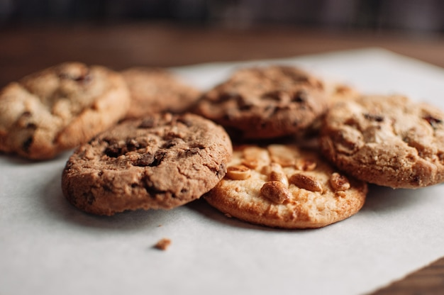Cookies empilhadas dos pedaços de chocolate na tabela de madeira em rústico, estilo country. bolinhos do chocolate no fim de madeira escuro do fundo acima.