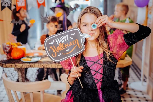 Cookies engraçados. colegial engraçada e fofa segurando biscoitos engraçados enquanto participava da festa de halloween com suas melhores amigas