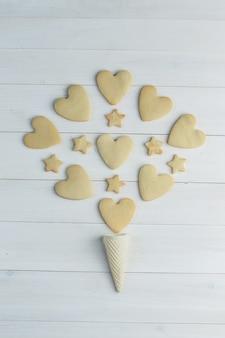 Cookies leigos planos com cone de waffle em fundo de madeira. vertical