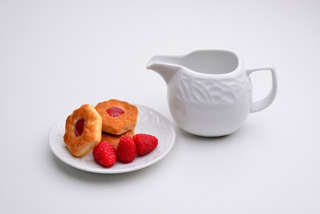 Cookies linzer com coração com geléia de framboesa em um prato branco com uma xícara