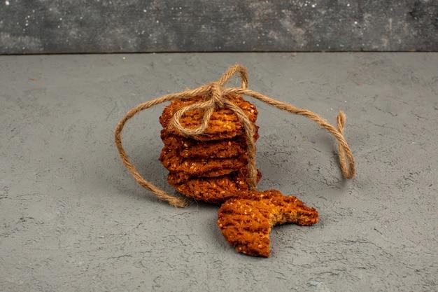 Cookies marrom saboroso doce sobre um piso cinzento
