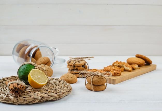 Cookies marrons em uma jarra de vidro com biscoitos em uma tábua e frutas cítricas em um jogo americano redondo na superfície branca