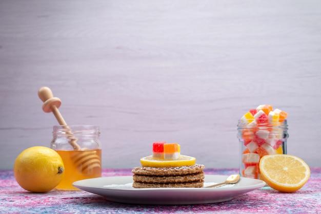 Cookies redondos de vista frontal junto com uma mesa de mel e limão