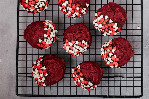 Cookies redondos vermelhos decorados com pó em forma de coração para o dia dos namorados, em uma grade de metal preta, fundo de pedra cinza