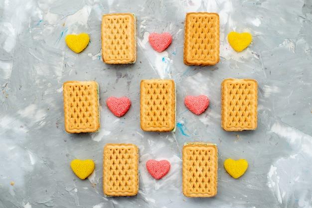 Cookies sanduíche com vista de cima e geleias coloridas em forma de coração na mesa branca.