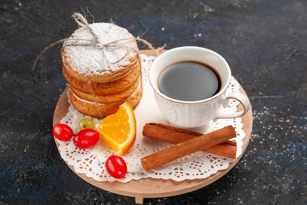 Cookies sanduíche de vista de cima de perto com recheio de creme, canela e café na superfície escura.