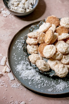 Cookies sem glúten de coco caseiro com flocos de coco na placa de cerâmica sobre a superfície de textura rosa. camada plana, espaço de cópia Foto Premium