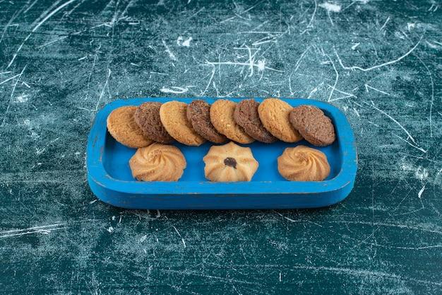 Cookies simples e de chocolate em uma bandeja de madeira, sobre o fundo azul. foto de alta qualidade