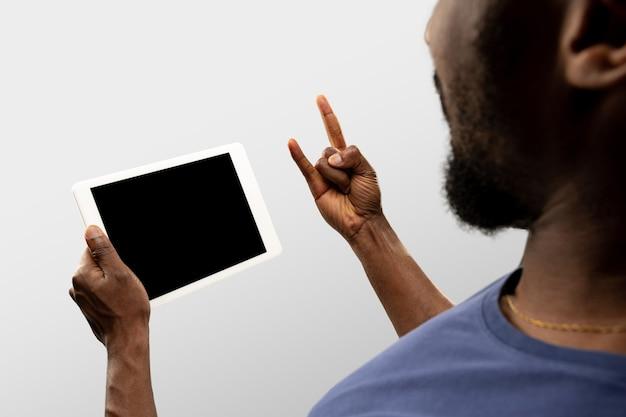 Cool, drive, rock horn. feche as mãos masculinas segurando um smartphone com tela em branco durante a exibição online de jogos de esporte popular, campeonatos. copyspace para anúncio. dispositivos, gadgets, conceitos de tecnologias