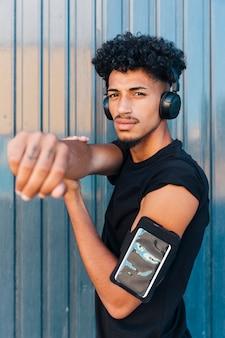 Cool étnica com braçadeira de telefone e fones de ouvido