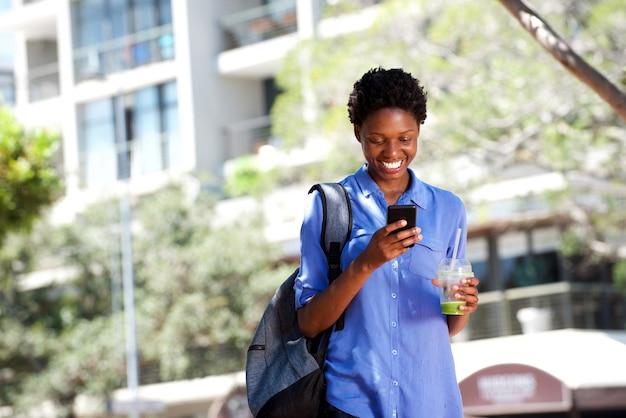 Cool jovem mulher africana andar ao ar livre na cidade usando telefone celular