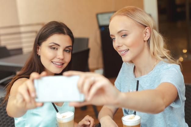 Cool meninas na moda tomando uma selfie na cafeteria