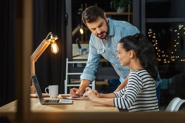 Cooperação agradável. bons, inteligentes e agradáveis colegas sentados no escritório e conversando enquanto trabalham juntos em um projeto