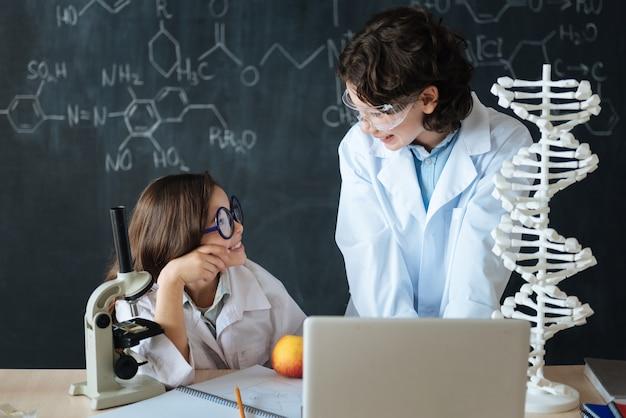Cooperação agradável com um amigo. alunos felizes, alegres e sorridentes, em pé no laboratório e explorando a ciência enquanto trabalham no projeto e usam dispositivos