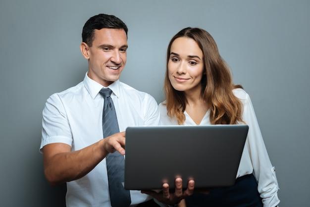 Cooperação agradável. homem simpático e agradável e alegre em pé com sua colega, mostrando uma foto a ela, segurando um laptop