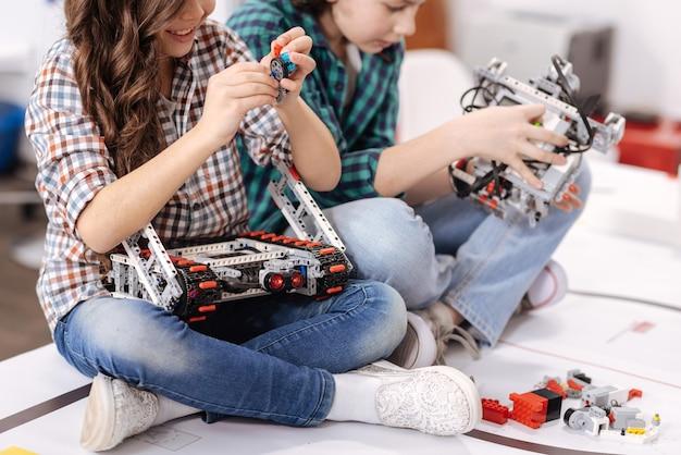 Cooperação em detalhes. sorrindo, amigos alegres e positivos sentados em casa construindo gadgets e dispositivos enquanto expressam positividade