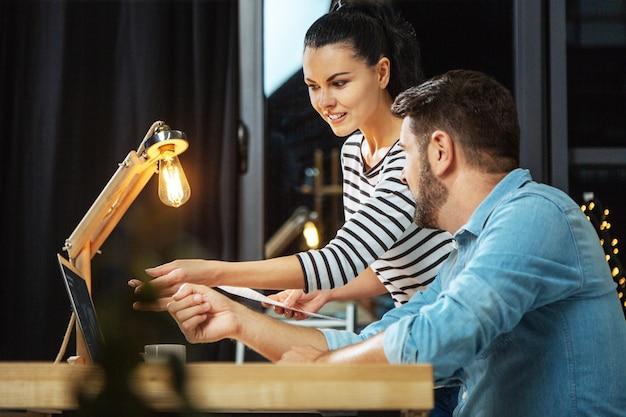 Cooperação profissional. mulher bonita alegre e simpática apontando para a tela e explicando sua ideia enquanto trabalhava com seu colega