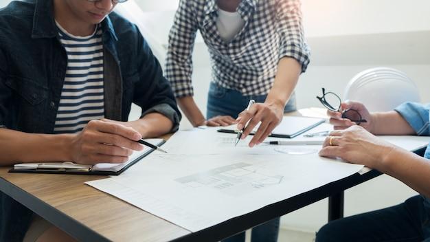 Coordenador que discute a reunião que trabalha no projeto do modelo arquitectónico no canteiro de obras.