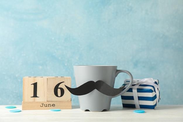 Copa com bigode decorativo, caixa de presente e calendário de madeira na mesa branca contra um fundo azul, espaço para texto