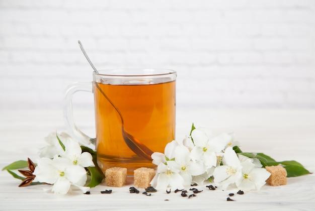 Copa com chá e flores de jasmim sobre um fundo branco