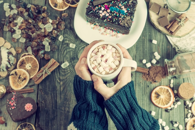 Copa com chocolate quente nas mãos femininas