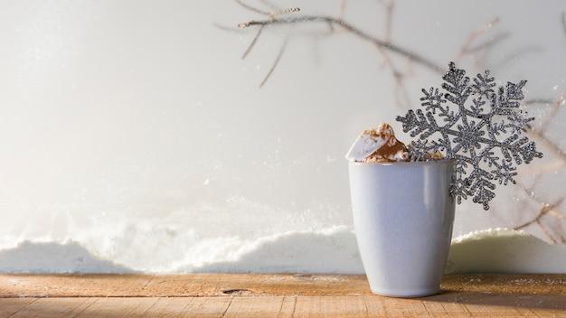 Copa com floco de neve de brinquedo na mesa de madeira perto do banco de neve