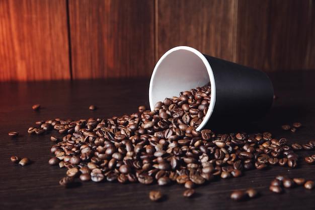 Copa com grãos de café marrons na mesa de madeira.