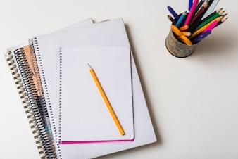 Copa com lápis perto de blocos de notas