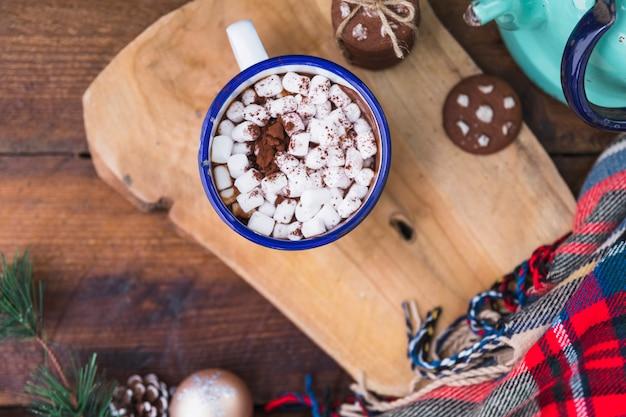 Copa com marshmallow perto de biscoitos e cachecol