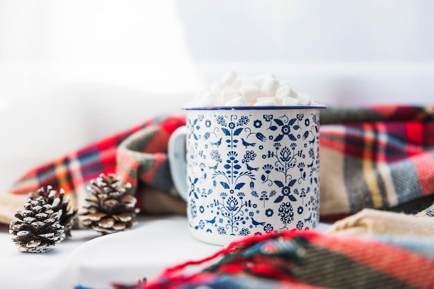 Copa com marshmallow perto de cachecol