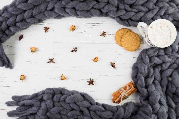 Copa com marshmallows perto de biscoitos e cachecol