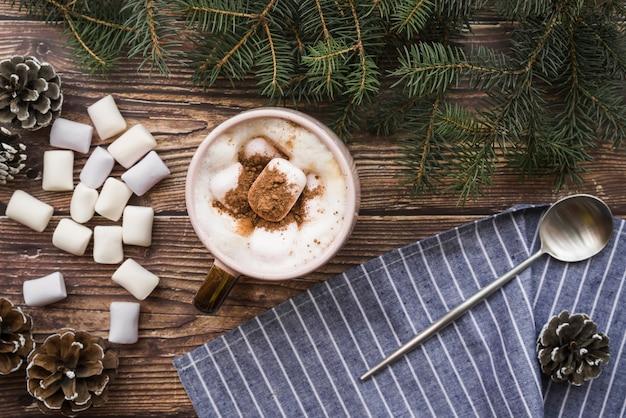 Copa com marshmallows perto de colher, galhos de abeto e senões