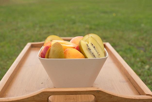 Copa de frutas fica em uma mesa de madeira.