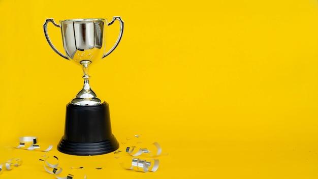Copa do campeonato troféu com fita e confetes em fundo amarelo para o vencedor do prêmio