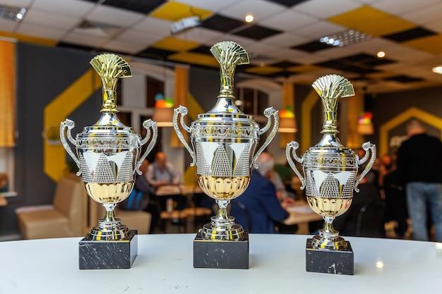 Copa do troféu de ouro vencedor ou campeão com fundo desfocado escuro abstrato. vitória em primeiro lugar de competição. conceito de vitória ou sucesso.