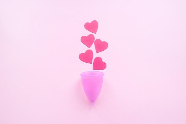 Copa menstrual reutilizável e corações vermelhos em rosa