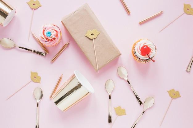 Copa perto de colheres, caixa e bolos