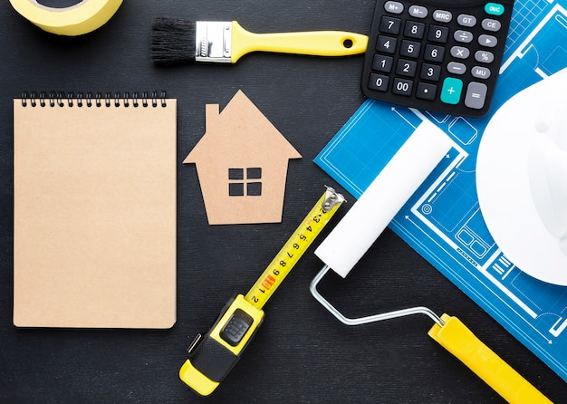 Cópia azul de uma casa com ferramentas e bloco de notas vazio