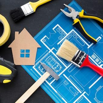 Cópia azul de uma casa com papelão e ferramentas de reparo