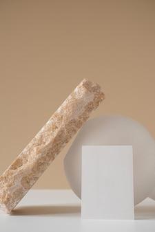 Cópia em branco cartão de papel com espaço, linda pedra de mármore rosa contra parede bege pastel