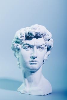 Cópia em gesso da escultura david michelangelo sobre fundo azul