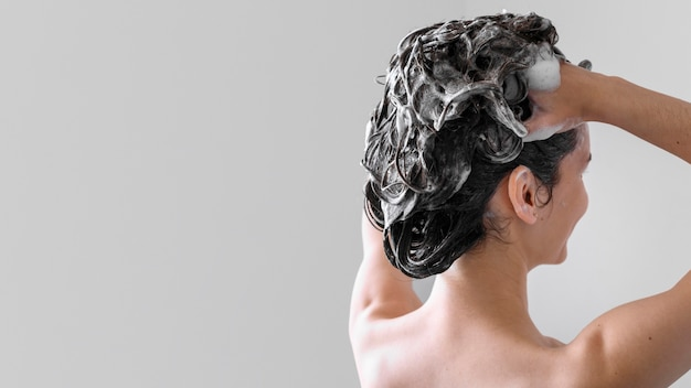Cópia-espaço feminino lavar o cabelo