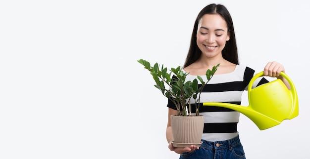 Cópia-espaço feminino rega flor
