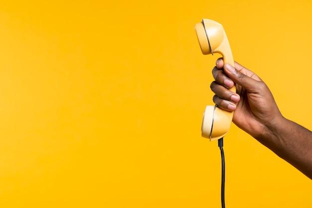 Cópia-espaço homem segurando o telefone antigo