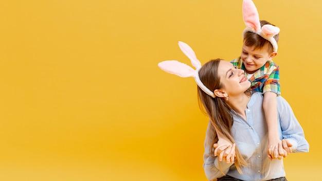 Cópia-espaço mãe e filho com orelhas de coelho, olhando um ao outro
