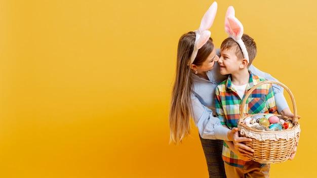 Cópia-espaço mãe e filho segurando cesta de ovos pintados