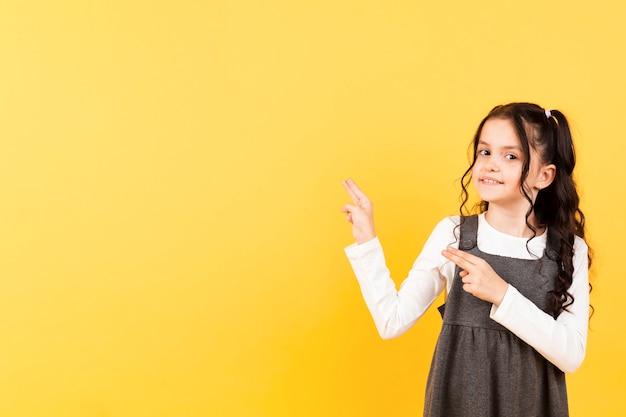 Cópia-espaço menina apontando pose
