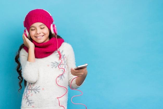 Cópia-espaço menina ouvindo maquete de música