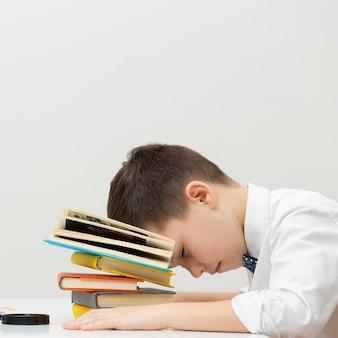 Cópia-espaço menino sentado com a cabeça nos livros