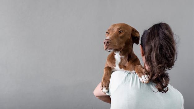 Cópia-espaço mulher segurando cachorro